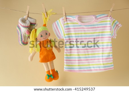 clothesline with toy doll and baby clothes - stock photo