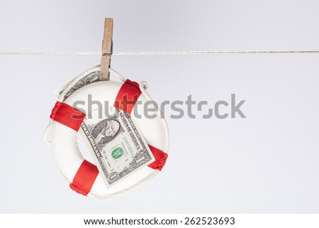 clothespin fixing a safety buoy with a one dollar banknote on a clothes line. financial concept for currency risk or protection  - stock photo