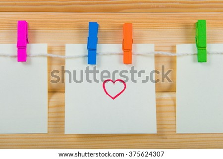 clothespin hanging with blank paper on wooden background. notes on color clothespin. Valentine's Day, the concept of love  - stock photo
