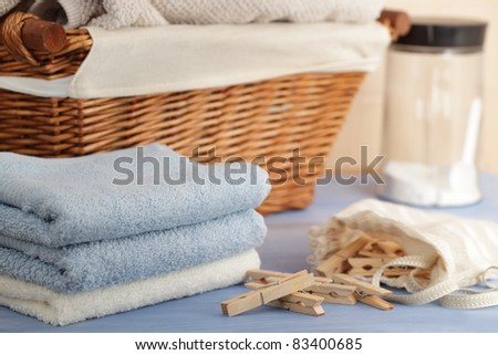 Clothespins in the bag, towels, laundry detergent, and a basket - stock photo