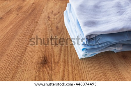 clothing, babyhood, motherhood and object concept - close up of pile of baby clothes for newborn boy folded on wooden table - stock photo
