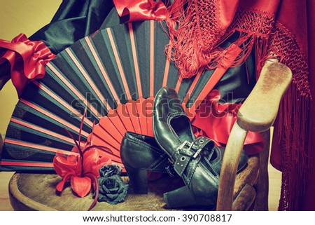 Clothing for Flamenco dance. Black shoes, fan, red scarf with tassels and paper roses are lying on a vintage wooden chair. Edited as a vintage photo with dark edges. - stock photo