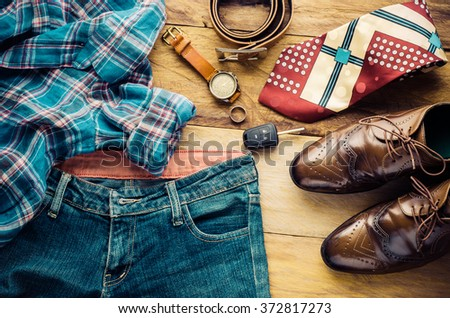 Clothing for men on wooden background - tone vintage - stock photo