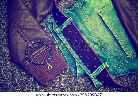 Clothing items and accessories: blue jeans with a leather belt, leather jacket, bracelet on the arm - stock photo