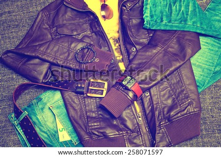 clothing items and accessories: blue jeans with a leather belt, leather jacket, T-shirt, watches, sunglasses and a bracelet on a hand - stock photo