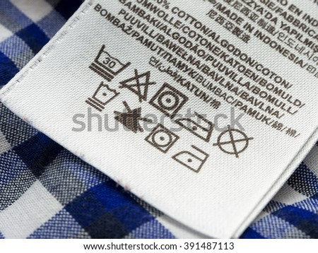 Clothing labels with laundry care symbols close-up. Shallow depth of field. - stock photo