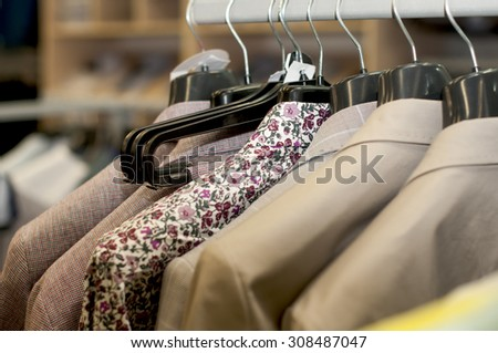 clothing on hangers in a shop. - stock photo