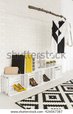 Clothing rack hanging on a wall and shoe racks made from wooden boxes, pattern black and white carpet - stock photo