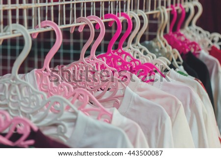 Clothing Store concept : hanging white and black shirts on hanger in clothing store for sale : beauty and fashion and business concept - stock photo