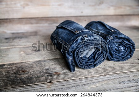 Clothing. twisted jeans on a wooden background - stock photo