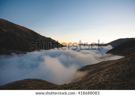 cloud between mountains at sunset - stock photo