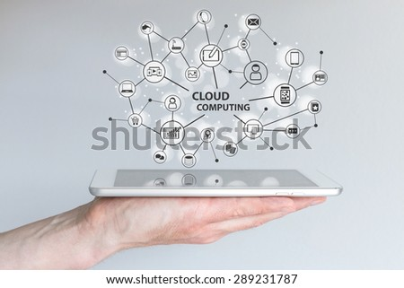 Cloud computing and mobile computing concept. Hand holding tablet or smart phone. Cloud network of connected devices and information. - stock photo