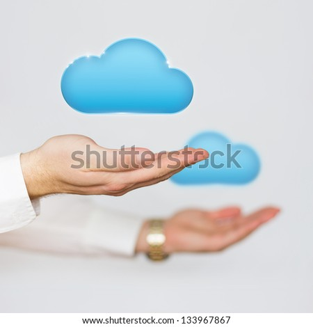 Cloud computing concept icons hovering over the hands of a businessman - stock photo
