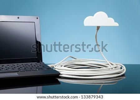 Cloud computing concept. Laptop connected to cloud via ethernet cable. - stock photo