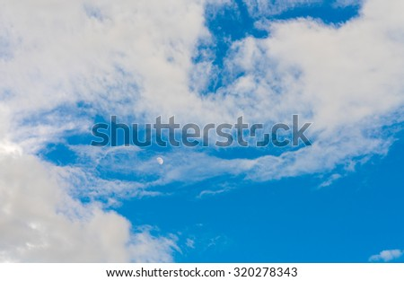 Cloud in blue sky with moon - stock photo