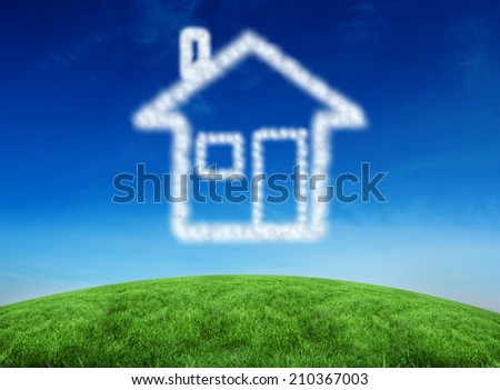 Cloud in shape of house against green hill under blue sky - stock photo