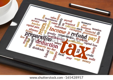 cloud  of words related to taxes, preparation, paying, income, refunds, on a digital tablet with a cup of tea - stock photo