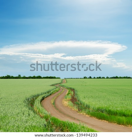 cloud over dirty road in green fields - stock photo