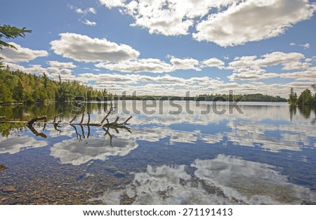 Cloud Reflections on a Calm Lake on a Sunny Fall Day in the Boundary Waters of Minnesota - stock photo