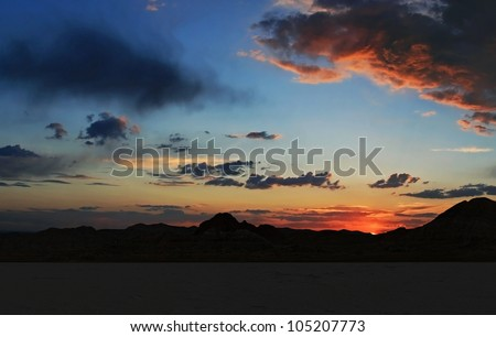Cloud scattered blue and orange brillant colored sunset over the Bonneville Salt Flats in the foreground with mountains behind. / Salt Flats Sunset / Harsh landscape, beautiful sunset. - stock photo