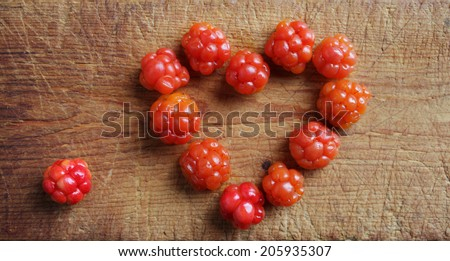 Cloudberries (Rubus chamaemorus) arranged in heart form on wooden cutting board. Closeup, daylight.  - stock photo