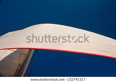 Cloudless blue sky with two white sails set.  Main sail and jib sail with red trim. horizontal image with copy space - stock photo