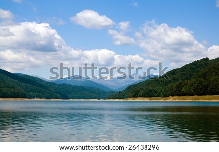 clouds above lake and trees on coast, distant mountains are showing their tops - stock photo