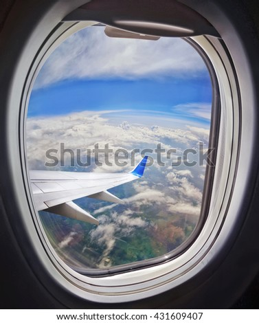 Clouds and sky as seen through window of an aircraft - stock photo