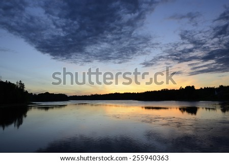 Clouds and Sky Reflecting in Water at Sunset - stock photo