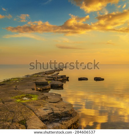 Clouds are reflected in the calm waters of Kimmeridge Bay at sunset - stock photo