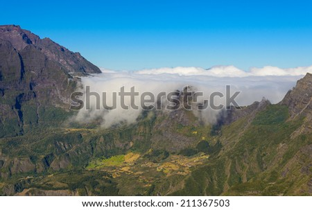 Clouds flowing above mountains in the Mafate cirque, La Reunion island - stock photo