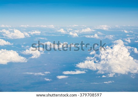Clouds in blue sky, aerial view from airplane window. - stock photo