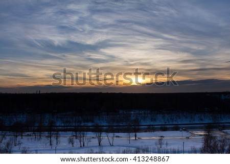 Clouds on the blue sky and winter forest - stock photo