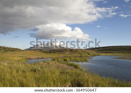 Clouds over a small lake in British Columbia in summer - stock photo