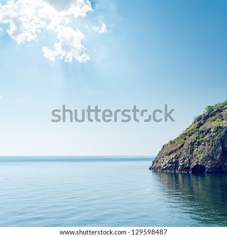 clouds over sea and cliff - stock photo