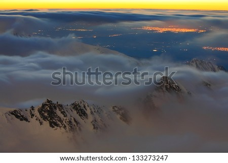 Clouds over the mountains and valley at night - stock photo
