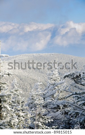 Clouds part over a snowy mountain on a cold winter day in vertical perspective - stock photo