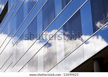 clouds reflected in glass from skyscraper - stock photo
