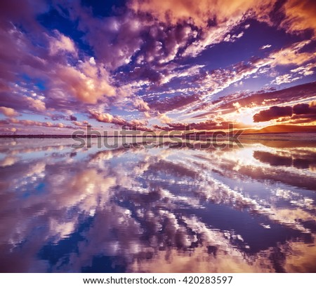 clouds reflected in the water at sunset, Sardinia - stock photo
