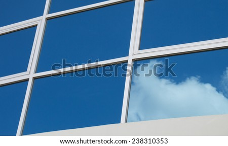 Clouds reflected in windows of modern office building - stock photo