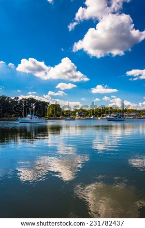 Clouds reflecting in the water at the harbor in Chesapeake City, Maryland. - stock photo