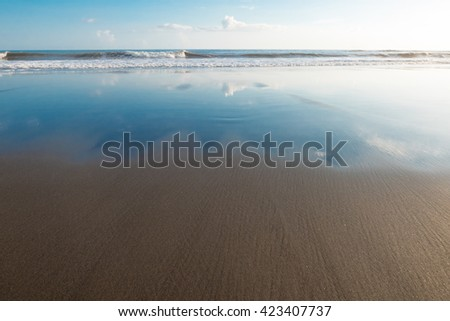 Clouds reflection in beach sand on Balian Beach in Indonesia with clear blue sky. - stock photo