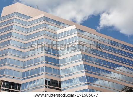 Clouds reflection in glass building - stock photo