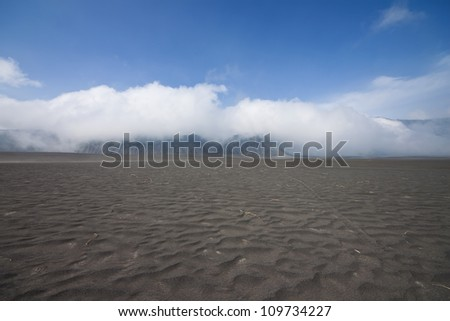 clouds roll over the mountain on black desert , Mt. Bromo,Indonesia. - stock photo