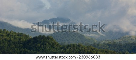 Clouds rolling in over high mountains on Panay island in the Philippines - stock photo