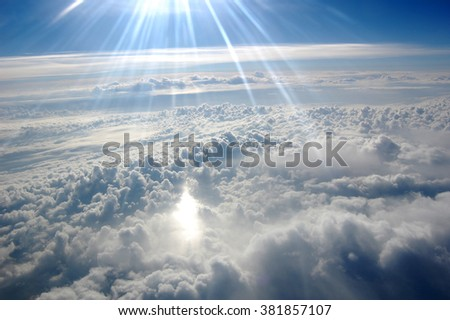 Clouds, sun, sky as seen through window of an aircraft - stock photo