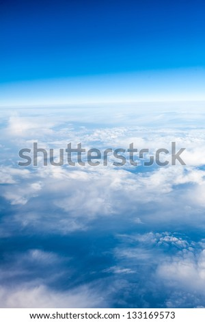 clouds. top view from the window of an airplane flying in the clouds. clear blue sky under high clouds located - stock photo
