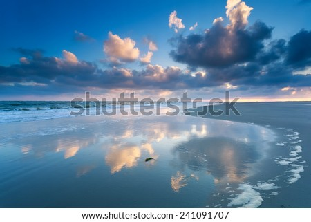 cloudscape reflected in North sea waves, Netherlands - stock photo