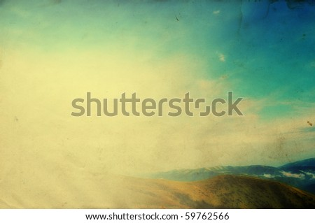 Cloudy blue sky upon green mountain ridge with added grunge retro effect texture - stock photo