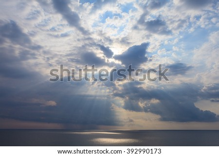 Cloudy Crimea seascape after storm seeing natural sunbeams at sunset. Sun rays shining through the clouds and reflected in the Black Sea. - stock photo
